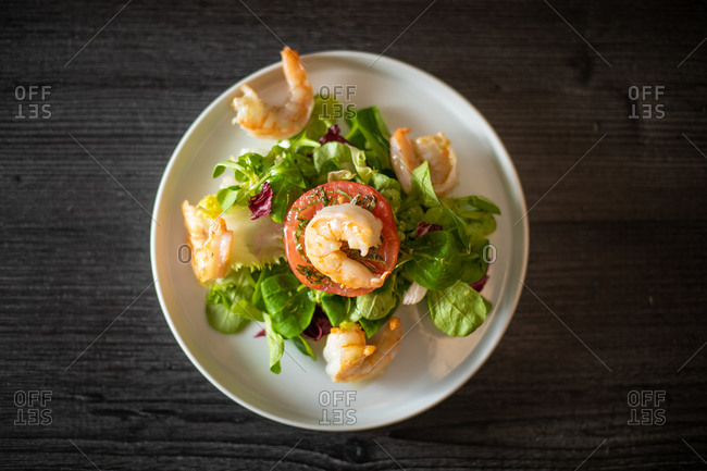 Top view of healthy spinach salad with shrimps and tomato served on withe ceramic plate on black table