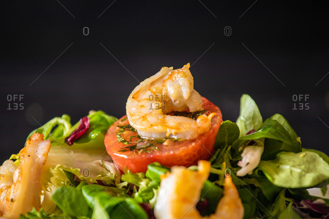 Closeup of healthy spinach salad with shrimps and tomato served on withe ceramic plate on black table