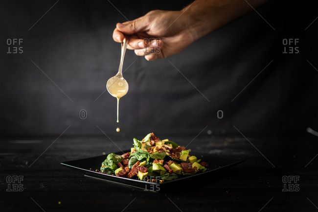 Unrecognizable cook adding spoonful of sauce into a yummy portion of palatable avocado salad with fresh spinach and walnuts served on square black plate on cafe table