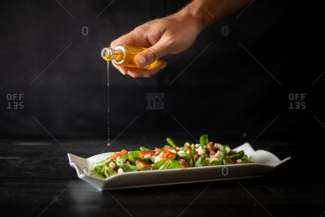 Unrecognizable chef spilling oil from small bottle on healthy spinach salad with tomatoes and mushrooms on black background