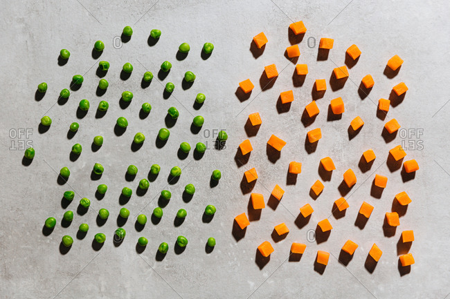 Overhead view of diced frozen peas and carrots on gray background
