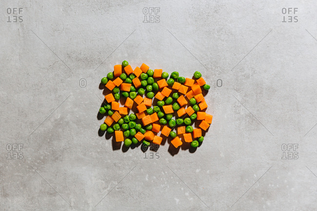 Frozen peas and diced carrots in a pile on gray background