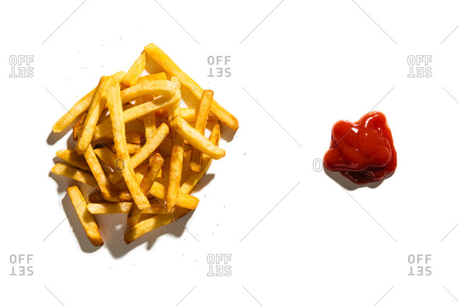 Salted French fries and ketchup on white background