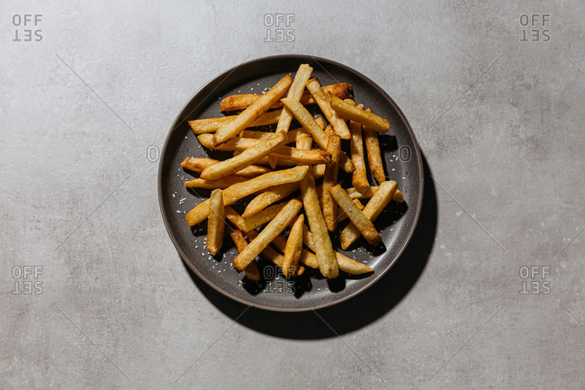 French fries with salt on gray plate