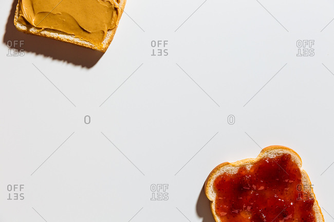 Preparation of peanut butter and jelly sandwich on white background