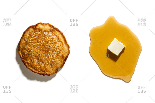 Pancake separated from syrup and butter on white background