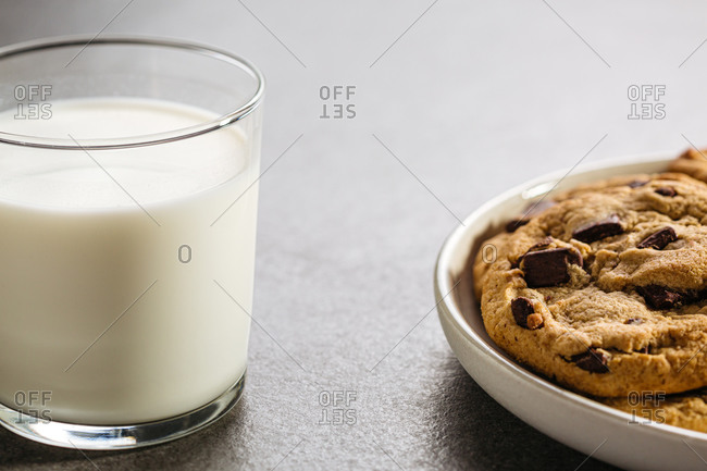 Close up of a glass of milk and plate of chocolate chip cookies