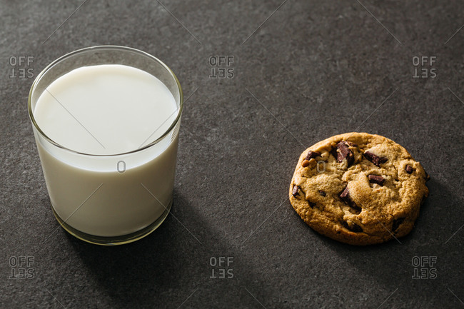A glass of milk and one chocolate chip cookie