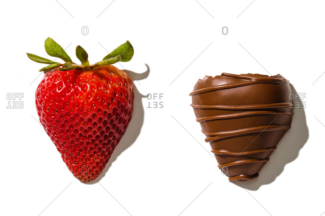Strawberry next to dipped chocolate coating on white background