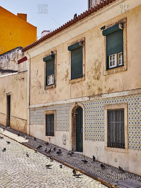 Lisbon, Portugal - July 19, 2019: Homes on slanted cobblestone street