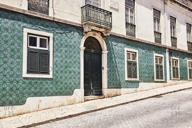 Lisbon, Portugal - July 19, 2019: Home with green tile on slanted cobblestone street