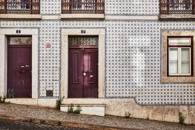 Lisbon, Portugal - July 20, 2019: Home with tile exterior and purple doors