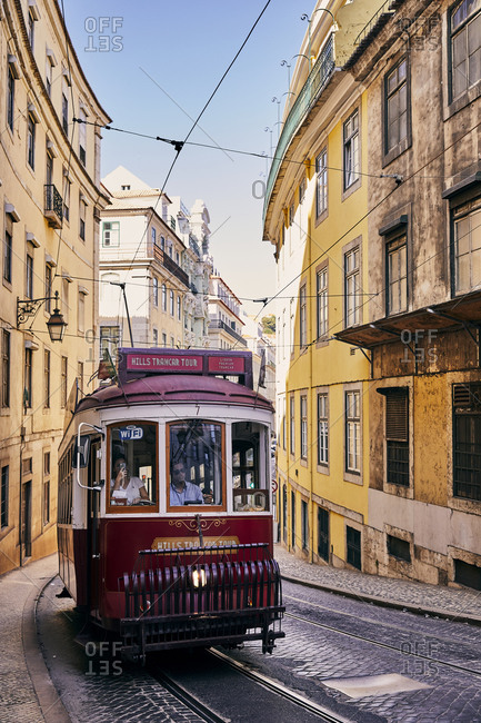 Lisbon, Portugal - July 20, 2019: Red tram car trolley on cobblestone street