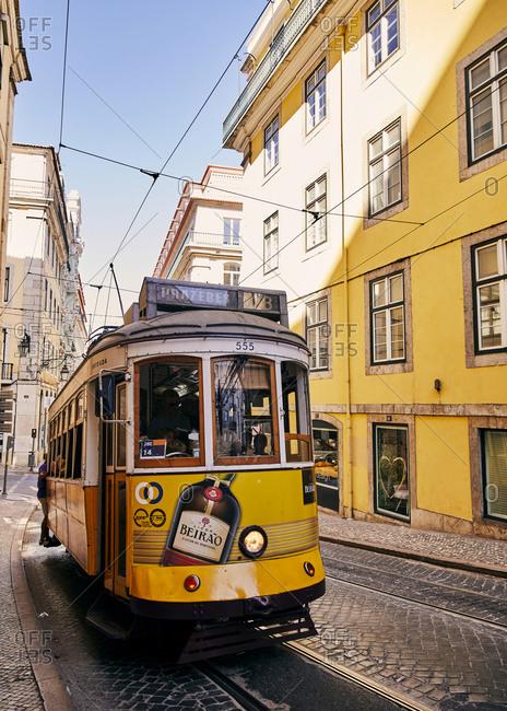 Lisbon, Portugal - July 20, 2019: Yellow tram car trolley on cobblestone street