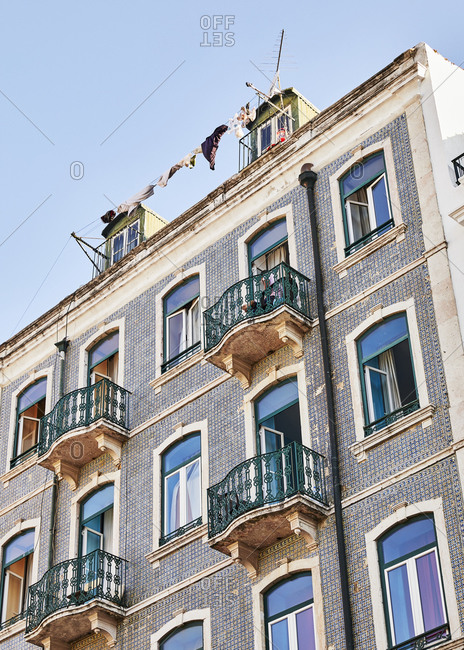 Low angle view of laundry hanging from tiled apartment building in Lisbon, Portugal