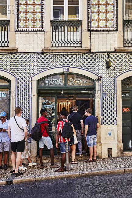 Lisbon, Portugal - July 21, 2019: Patrons waiting outside of a gelato shop