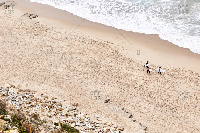Portugal - July 23, 2019: Bird's eye view over men walking on sandy beach with surf boards