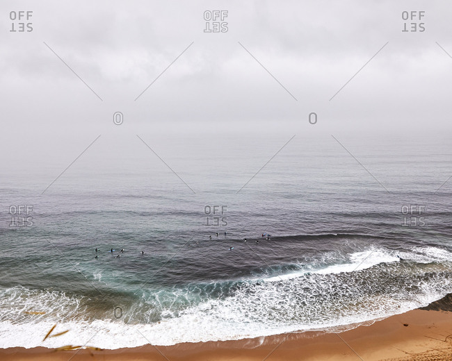 Group of surfers in the ocean off the coast of Portugal