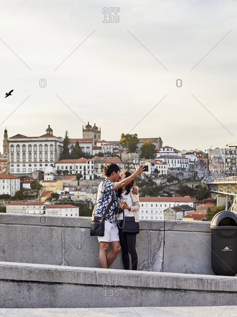 Porto, Portugal - July 30, 2019: Couple taking selfie while kissing