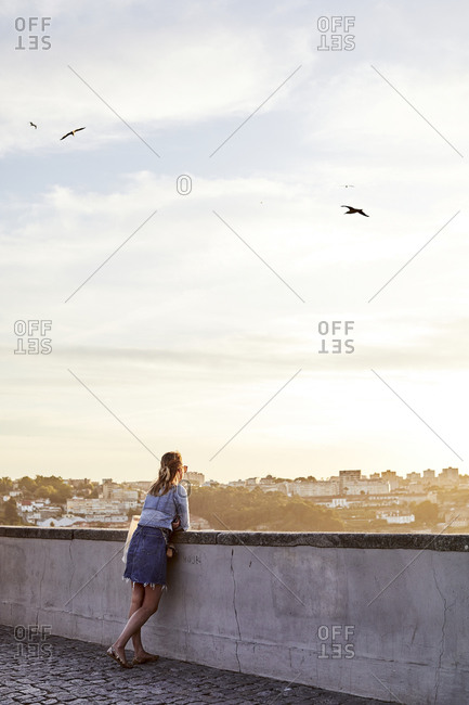 Porto, Portugal - July 30, 2019: Woman looking over city watching the sunset