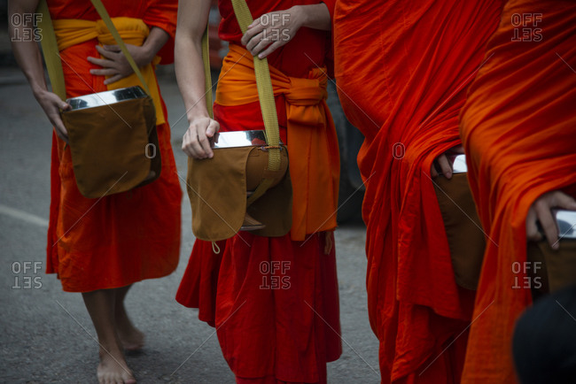 Buddhist monks take to the streets to receive sticky rice from locals during an early morning daily ritual known as Sai Bat (morning alms) in Luang Prabang, Laos