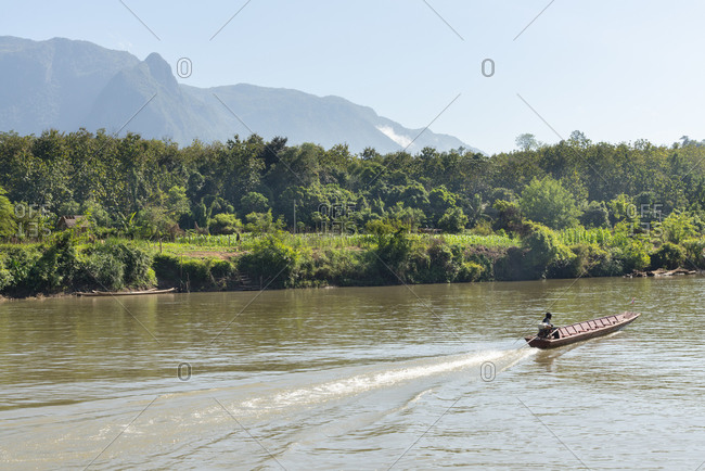 A boat cuts across the river in a bucolic area of Laos