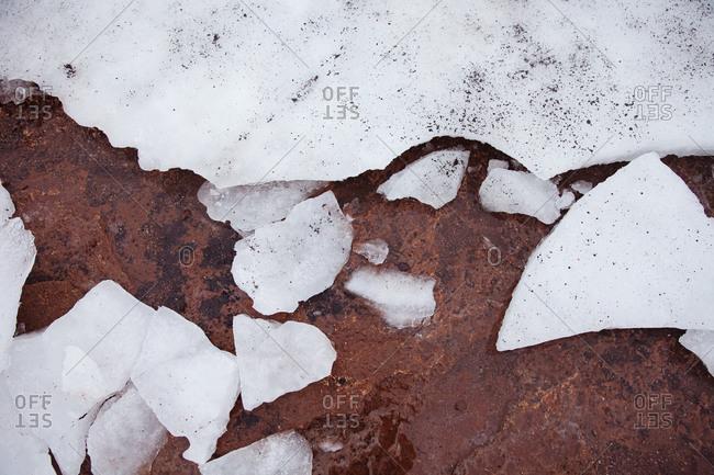Broken ice on brown rock