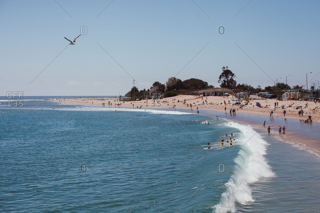 Waves rolling into a beach filled with tourists in the summertime