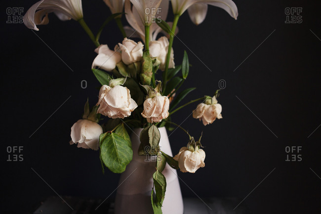 White floral arrangement with wilting roses