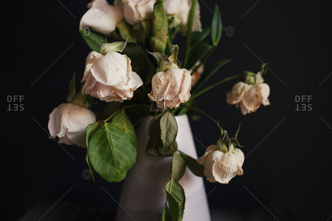 close up of white floral arrangement with wilting roses