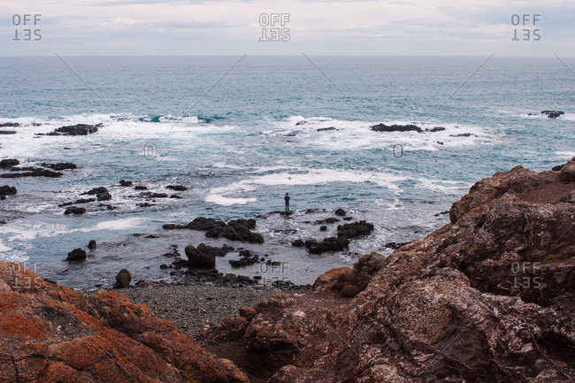 Man standing on rock looking out at the ocean