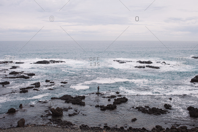 Man standing on rocky beach looking out at the ocean