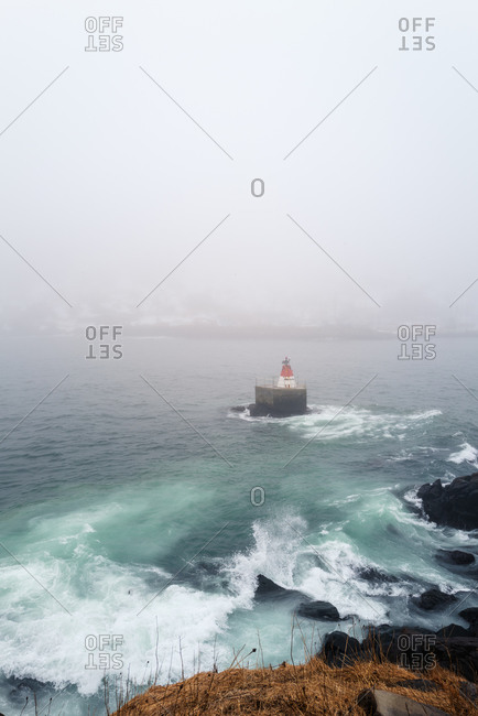 Lighthouse in the ocean on a foggy day