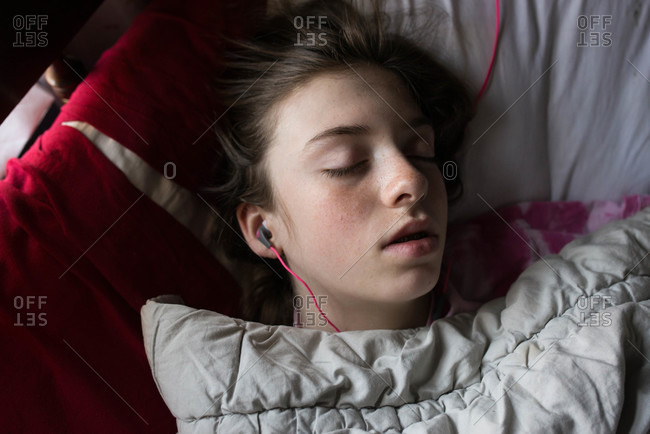 Young teen sleeps with headphones in her ears