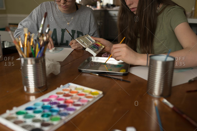 Two girls paint with watercolors