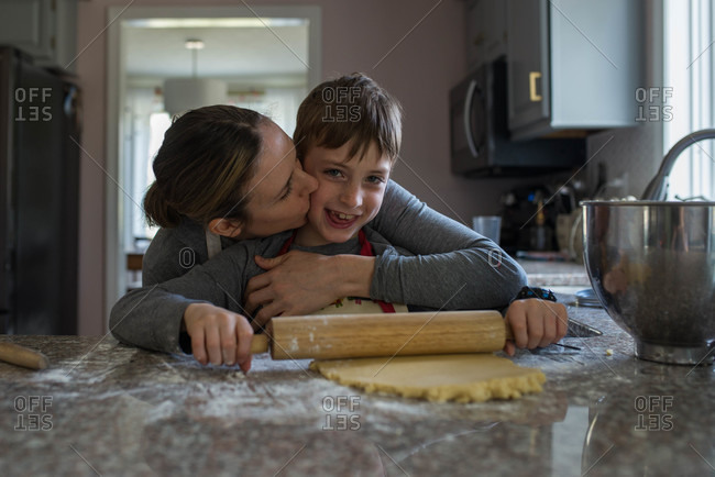 Mother kisses son while he rolls out cookie dough