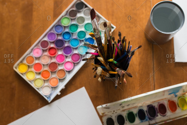 Paintbrushes and watercolor paints on table