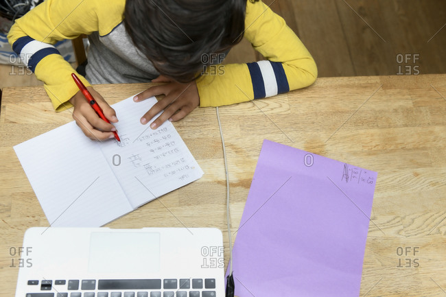 Overhead view of student working on assignments in homeschool
