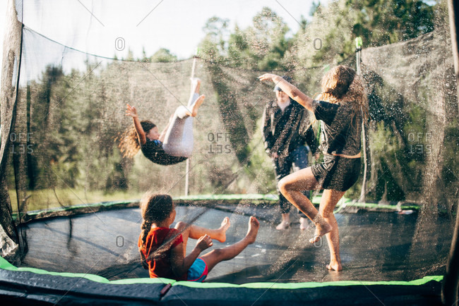 Kids jumping together on a backyard trampoline with net