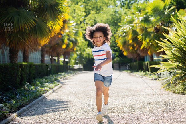 Tween girl with afro hair running in a park
