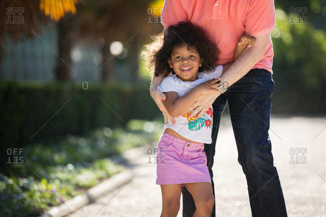 Happy little girl with afro hair with her Dad's arms wrapped around her