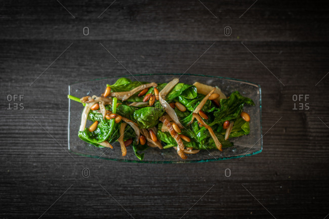 From above glass plate of tasty spinach salad with mushrooms placed on black wooden table in cafe