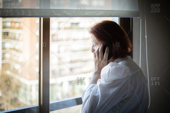 Side view of senior female in white blouse having phone call while standing near window in hospital ward visiting relative