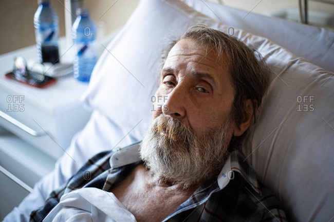 Calm aged man with beard lying under blanket on bed in hospital ward looking at camera