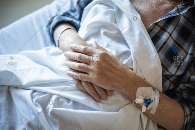 From above crop elderly patient with intravenous catheter in arm lying under blanket and sleeping
