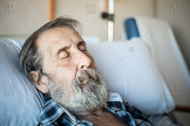 Calm aged man with beard lying under blanket on bed in hospital ward and sleeping
