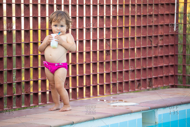 Cute little child in panties sipping fresh beverage through straw and looking at camera while standing on poolside