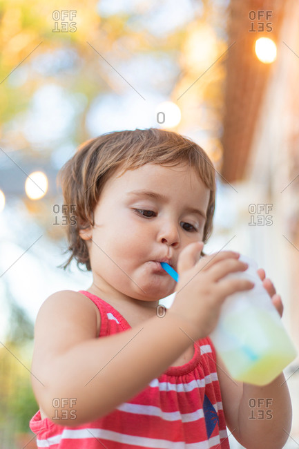 Cute little child sipping fresh beverage through straw and looking away with blurred lights on the background