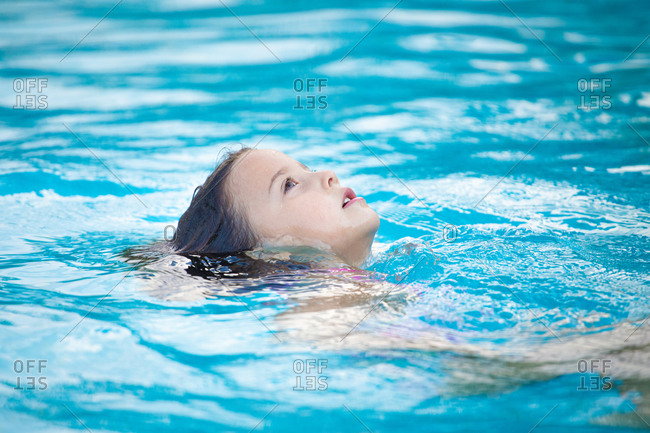 Cute girl floating on back in clean water and looking up while spending time in pool