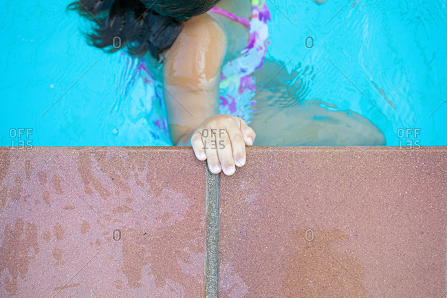 From above anonymous kid keeping hand on border and swimming in clean water of pool